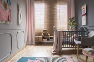 Blinds on windows in child's bedroom interior with pink blanket on bed.