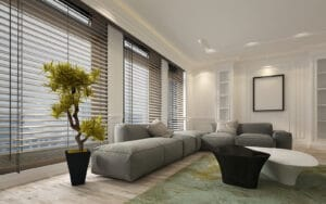 Luxurious living room with grey sofa and window installed with venetian blinds