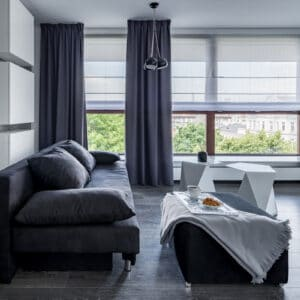 Grey living room with sofa, coffee table and window covered with blinds and curtains