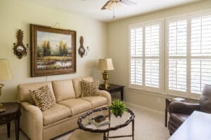 Spacious living room with leather sofa set and plantation shutter windows